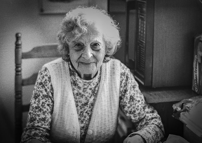 My grandmother Amelia sitting in her kitchen.
